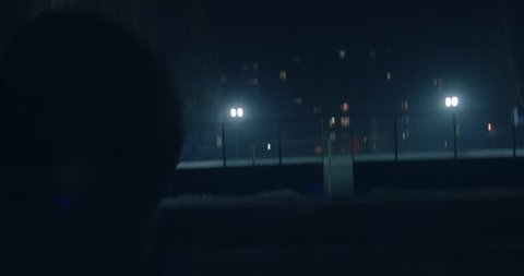 Scene: Street sports at night. A man enters the stadium, lit by searchlights. Background of multi-storey houses with luminous windows. Close-up. The camera follows the person.