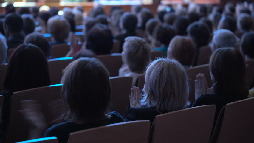 A lot of viewers are applauding closeup indoor Philharmonic Society. Crowded hall close up. Satisfaction of auditorium. Successful submission and expressive ovation. Muted lighting. All seats are busy | Shutterstock HD Video #25171220