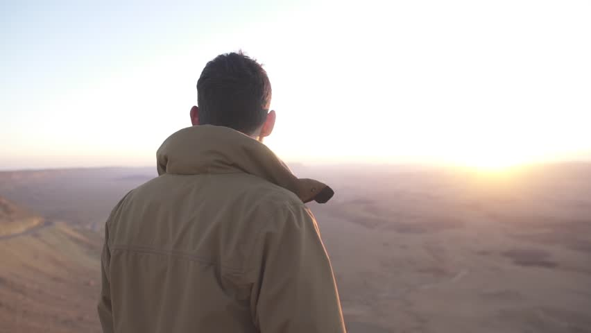 Man looking at the view of the desert under the morning sunlight | Shutterstock HD Video #25189457