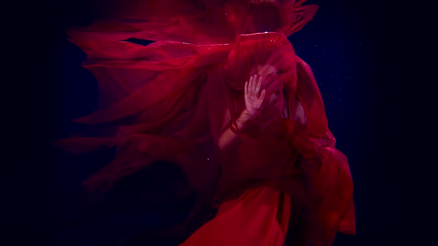Slow motion dancing girl artist under water. For a red cloth to the light with his hands and face.