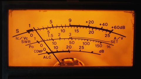 Dial Indicator Gauge Of The Transceiver and Signal Level Meter. Dial gauge modes transceiver radio stations close-up. Bright orange, yellow lights. Analog signal indicator.