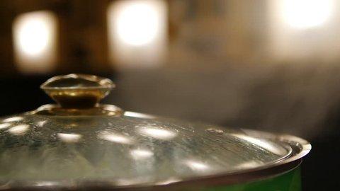 Closeup of lady hand opening steam sukiyaki pot lid