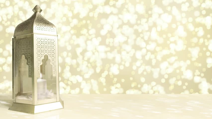Arabic ornamental lantern with burning candle and glittering golden background with falling bokeh lights. Ramadan HD footage.