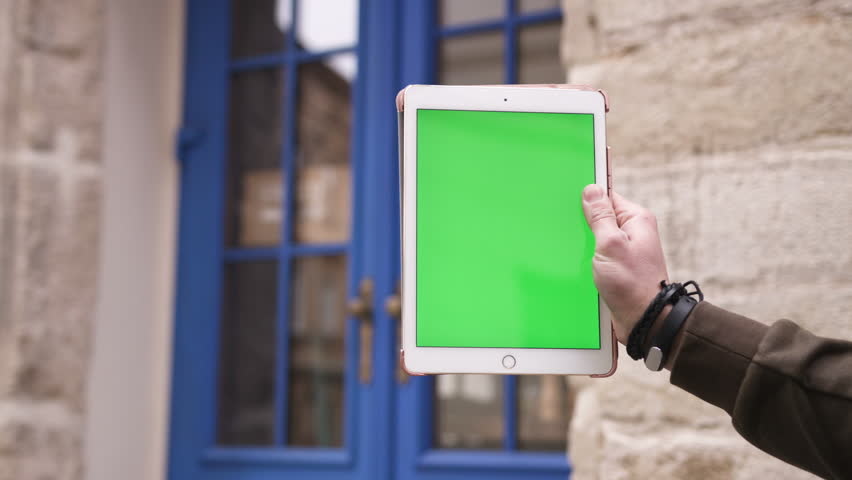 Closeup Hand Of Man Holding Tablet Computer With Vertical Green Screen In The Background Blue Door