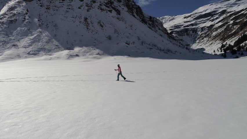 Aerial view of woman cross-country skiing on fresh snow near mountains | Shutterstock HD Video #25242827