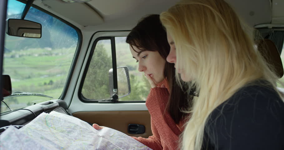 Two young woman reading Road Map in car planning European holiday Summer Vacation traveling in hippie van on road trip
