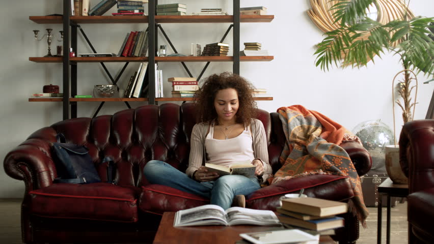 Young happy Latin woman read interesting paper book for education sitting alone on comfort leather sofa in the cozy living room at home with bookshelf near window during sunny day | Shutterstock HD Video #25278647