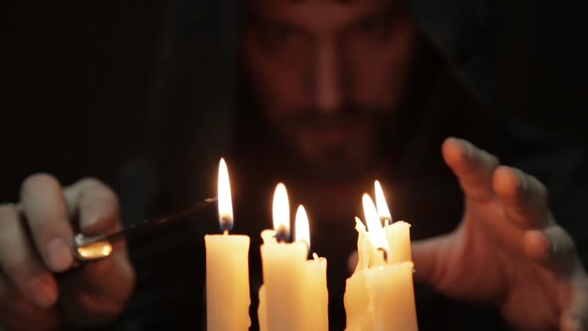 man doing the magic ritual. close-up several candle and old book. necromancer casts spells from thick ancient book by candlelight