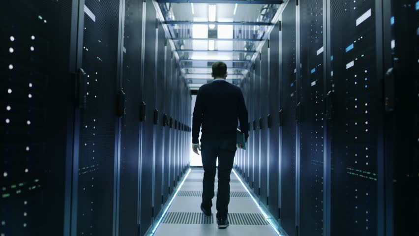 Back View of IT Engineer Walking Through Data Center with Working Rack Servers. Shot on RED EPIC-W 8K Helium Cinema Camera. | Shutterstock HD Video #25323347