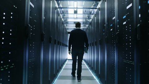 Back View of IT Engineer Walking Through Data Center with Working Rack Servers. Shot on RED EPIC-W 8K Helium Cinema Camera.