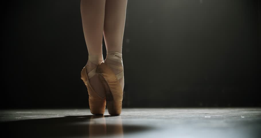 Slow motion close up shot of a ballet dancers feet as she practices in the dark studio