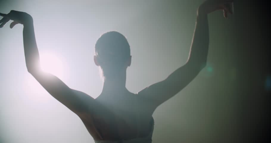 Ballerina dances on stage, close-up with magic light and smoke on the background, slow motion
