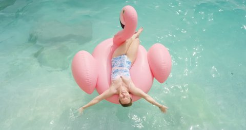 Woman lying on inflatable flamingo relaxing floating in ocean Happy girl enjoying summer vacation on tropical island holiday tanning beautiful toned beach body wearing bikini