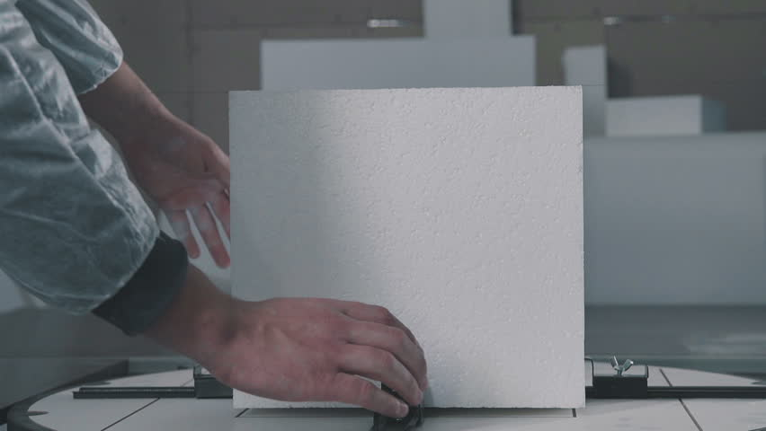 Close up: Cutting plastic foam. Cube of expanded polystyrene foam. Cutting out volumetric letters of foam plastic. Figured cutting of foam plastic. Creation of a volumetric inscription (logotype).