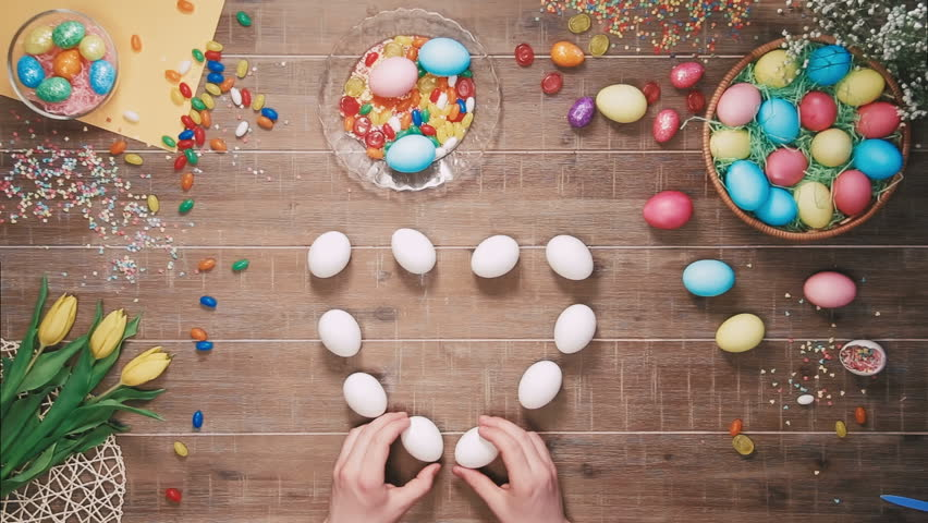 Man making heart shape with easter eggs on table decorated with easter eggs. Top view | Shutterstock HD Video #25342937