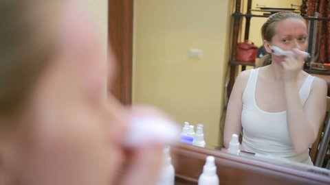 Mesotherapy at home. Girl mesorollerom handles the face of the house in front of the mirror