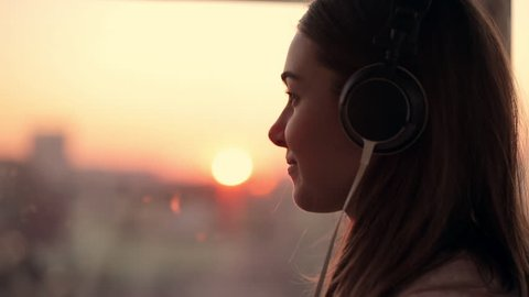 Attractive young woman wears listening to music on the smartphone at city blurred background with sunset. enjoying the tunes in her headphones