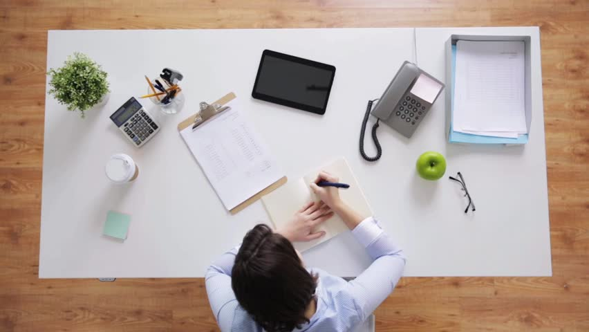 business, people and work concept - businesswoman with papers writing to notebook at office desk #25382537