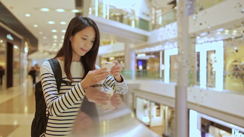 Young Woman use of mobile phone in shopping mall | Shutterstock HD Video #25384433