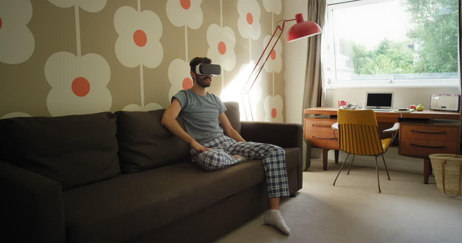 Young man wearing virtual reality headset sitting on sofa at home watching 360 video imagination concept | Shutterstock HD Video #25398977