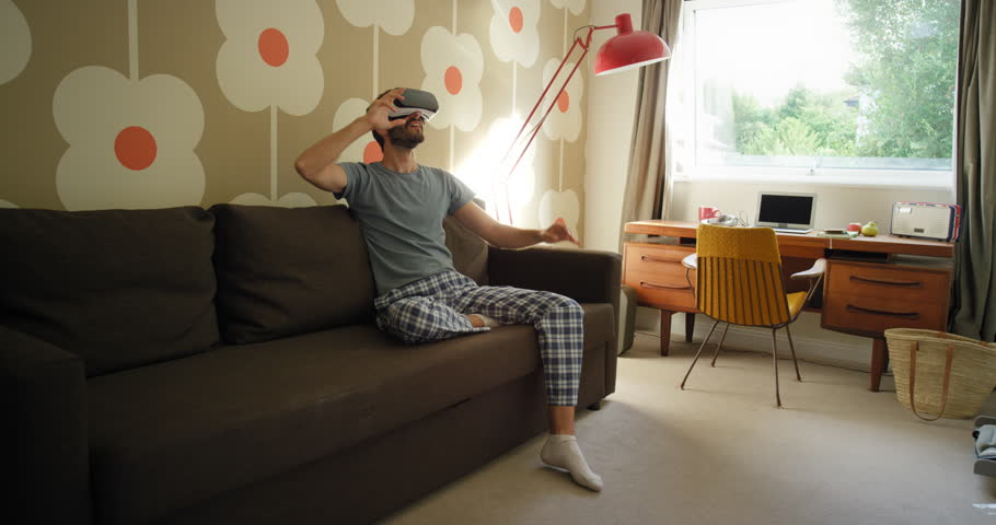 82ff6d2f1a9 Young man wearing virtual reality headset sitting on sofa at home watching  360 video imagination concept