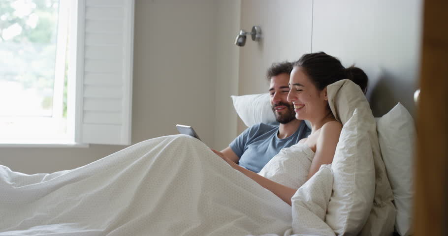 young couple lying in bed using smartphone digital tablet technology scrolling online browsing sharing real moment