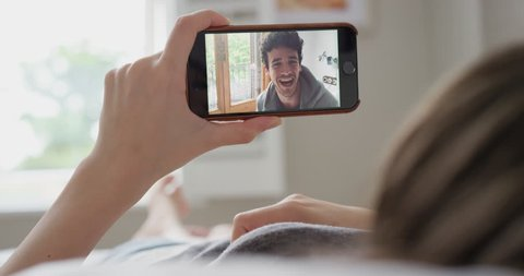 Young woman having video chat holding smartphone webcam chatting to friend lying in bed at home