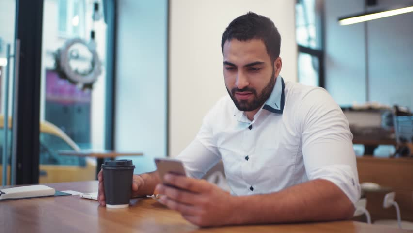 Amazing man holding a cup of coffee, and smiling towards the phone screen. Everyday routine, social networks. Using gadget. Successful lifestyle. | Shutterstock HD Video #25411724