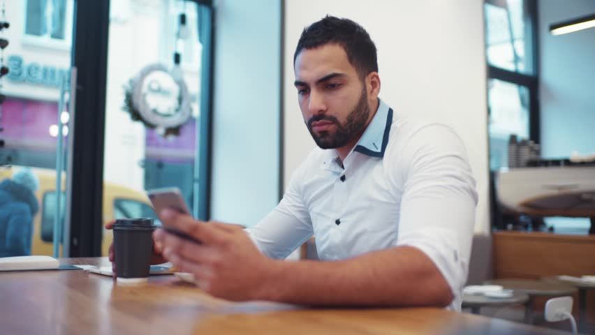 Handsome bearded man in a white formal shirt is using his phone for the internet surfing while drinking coffee. Modern life, businessman. Smartphone, social networks. | Shutterstock HD Video #25411757