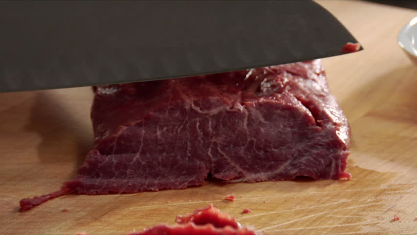 Close-up of chef slicing a few pieces of steam and placing with other slices.