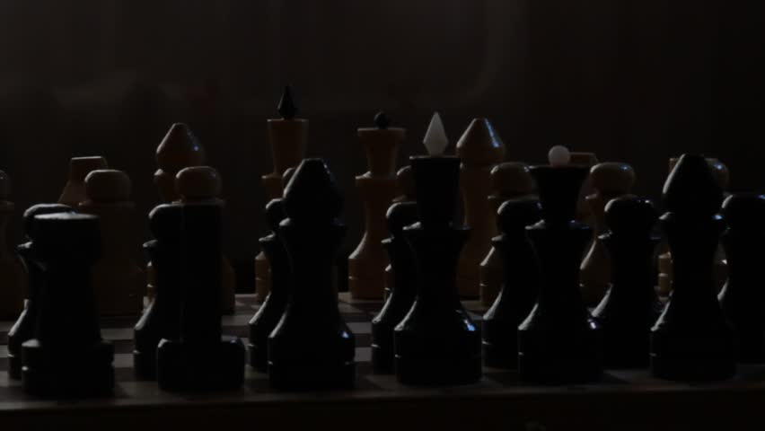 Chessboard with chess pieces in the darkness against a black background. The rotating footage. Chess dramatic battle concept.   Shutterstock HD Video #25424357