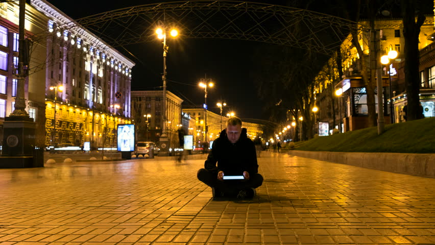 Young man sitting on the sidewalk with tablet in hands. Surrounded by walkers on public street. Time lapse. | Shutterstock HD Video #25424927