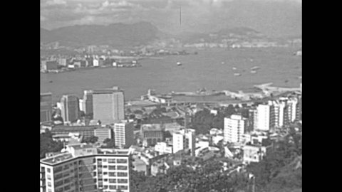 Aerial view of Victoria Harbour skyline from overlook on top of the Peak Tower, icon building in Hong Kong. Historic restored footage on 1980s with boats and buildings.
