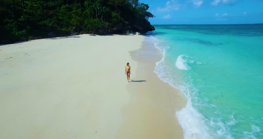 Female model walking on white sand beach