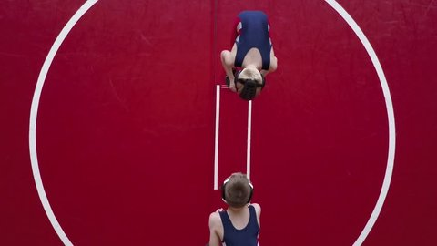 Two youth wrestlers filmed from overhead.