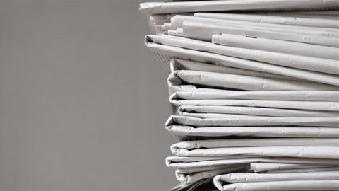 pile of newspapers, tracking shot of a stack of journals