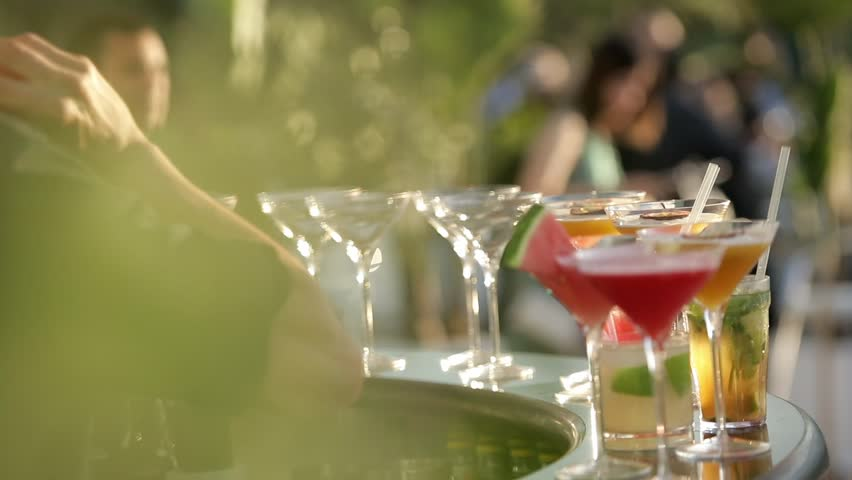 Decorating red cocktail with slice of watermelon. Cosmopolitan and Margarita cocktails on a bar. Party time. Bartender pouring alcohol into beautiful glass outdoors on a sunny, warm summer day.