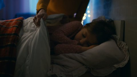 Sweet Little Girl Sleeps in Her Bed at Night, Her Mother Tucks Her Blanket in. Shot on RED EPIC-W 8K Helium Cinema Camera.