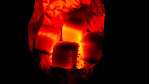 Hot coals in the hookah bowl in darkness closeup. Time lapse video 4k.