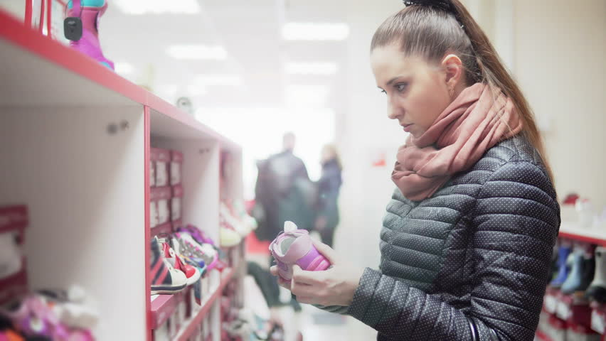 Young attractive woman is choosing children's shoes in a store. She is looking at the children's shoes and comparing them. 4K | Shutterstock HD Video #25554047
