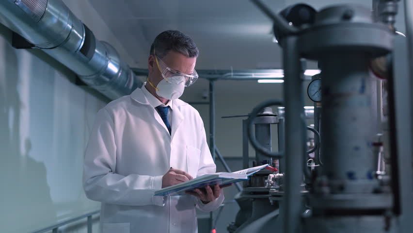 An engineer with the notepad wearing the mask inspecting the plant. | Shutterstock HD Video #25555457