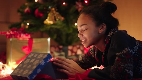 Young black woman is openning a gift box with red ribbon on New Years night
