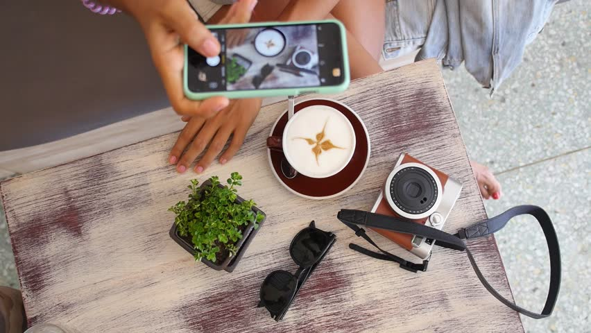 Female Taking Pictures With Smartphone of Cup of Coffee