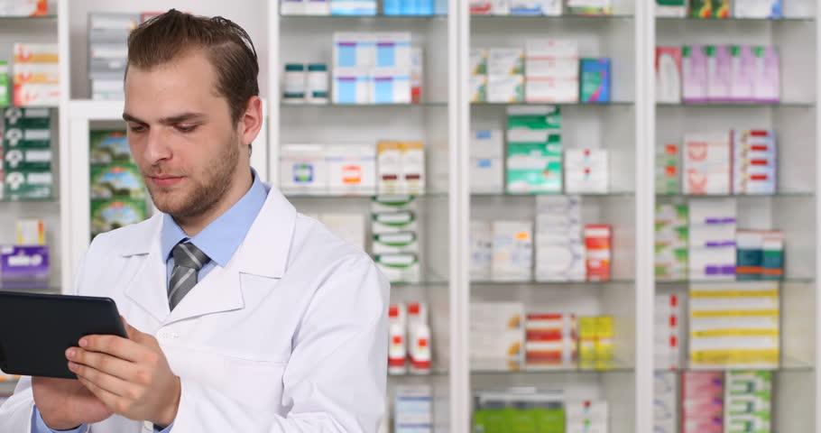 positive pharmacist man using digital tablet ordering drugs pharmacy activity 4k stock footage clip - Drug Information Pharmacist