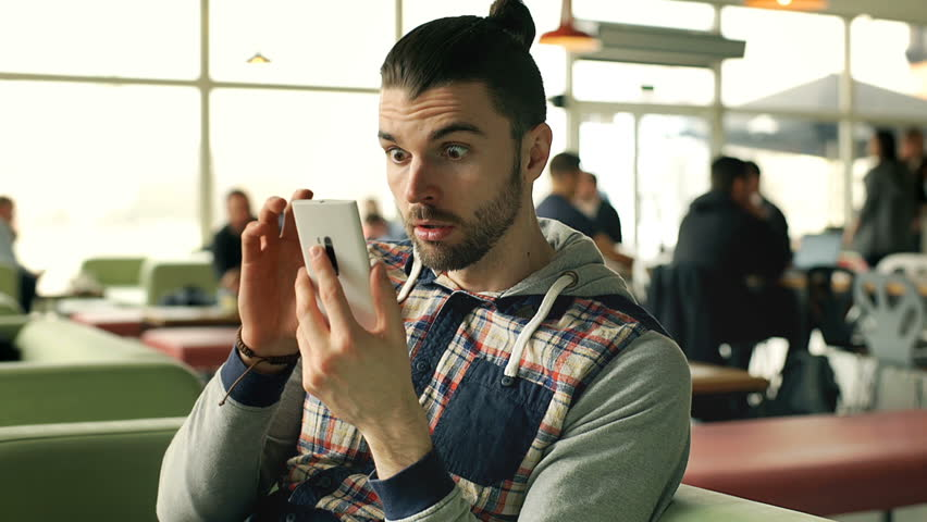 Man looks shocked while having received very bad news on smartphone, steadycam shot