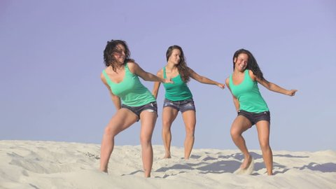 Team of pretty energetic girls dancing on the sand together