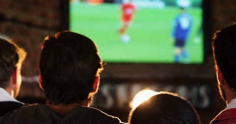 Excited friends watching soccer match while having beer in bar