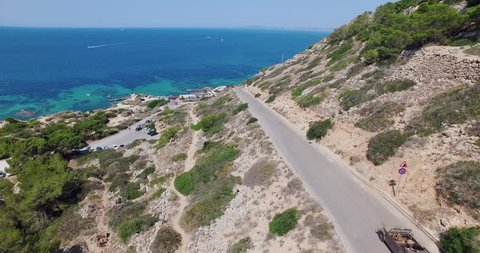 Drone flight at midday sun over Palma de Mallorca following car on coast street