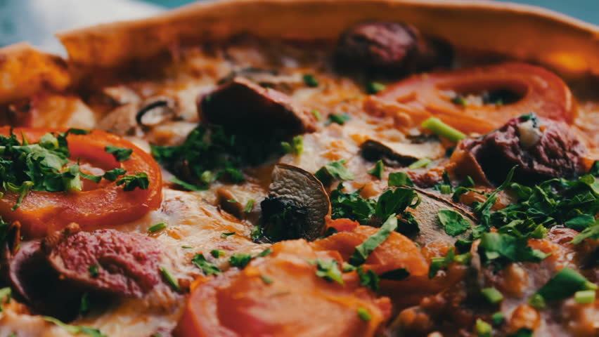 Pizza with hunting sausage, tomato, herbs and cheese close up view. slice of pizza,melted cheese dripping.Delicious italian pizzas