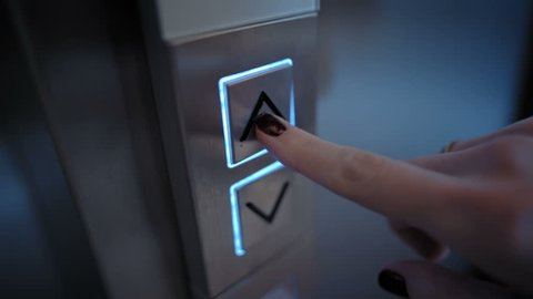 Young Woman Presses a Button of Lift to go Up by a Finger with a Painted Nail